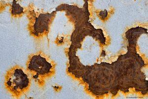 Rost blättert an alter Metallplatte ab